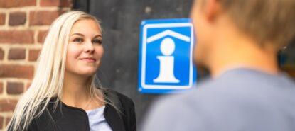 nainen matkailuinfon ovella