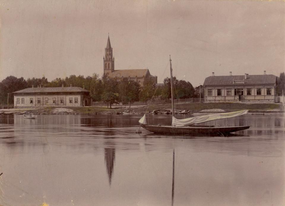 Laiva lipuu kaupungin edustalla vanhassa valokuvassa