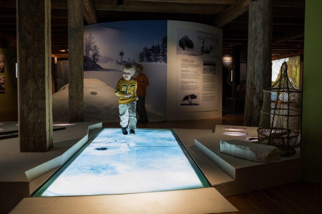 lapsi kulkee museonäyttelyn jäätietä pitkin