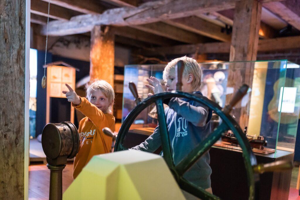 lapset pyörittävät laivan ruoria