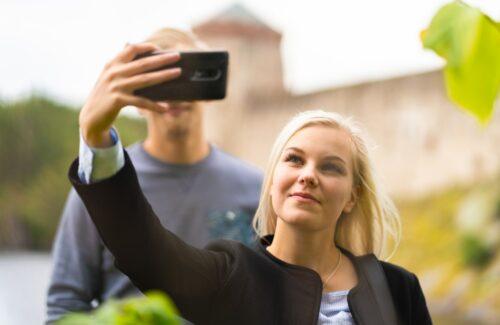 nainen kuvaa itseään Olavinlinnan edustalla